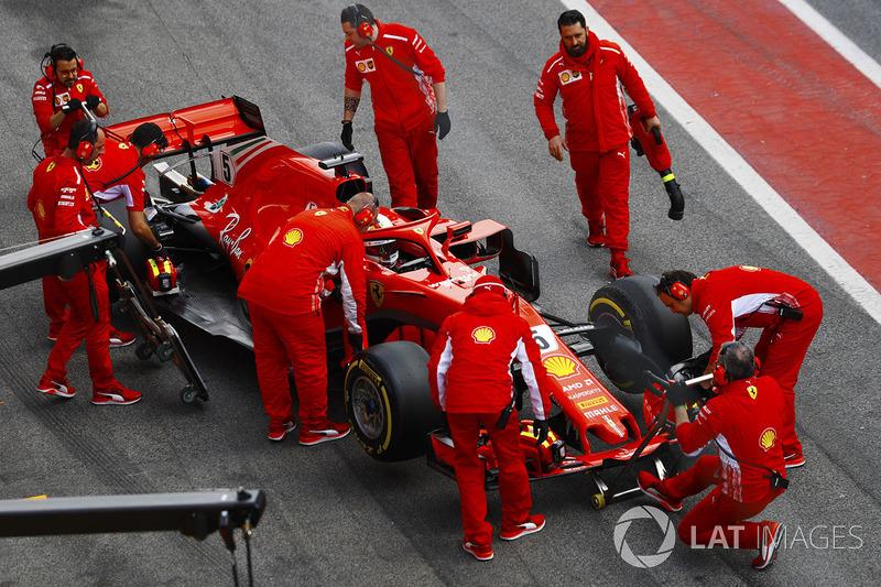 Sebastian Vettel, Ferrari SF71H, is attended to by mechanics in the pit lane