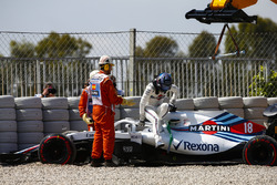 Lance Stroll, Williams FW41, climbs out of his car and is assisted by marshals after spinning into the gravel