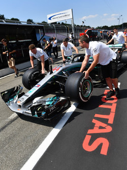Un mécanicien avec la Mercedes-AMG F1 W09 dans la pitlane