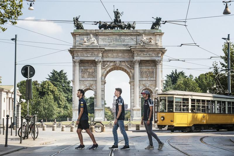 Daniel Ricciardo, Carlos Sainz Jr. and Daniil Kvjat are crossing the street in front of Arco della Pace