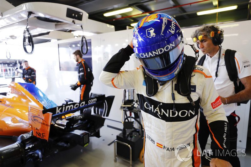 Fernando Alonso, McLaren, puts on his helmet in the garage