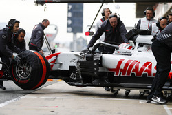 Kevin Magnussen, Haas F1 Team, is attended to by mechanics in the pit lane