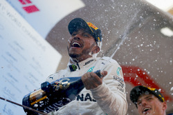 Lewis Hamilton, Mercedes AMG F1 W09, celebrates victory by spraying champagne with Max Verstappen, Red Bull Racing, on the podium
