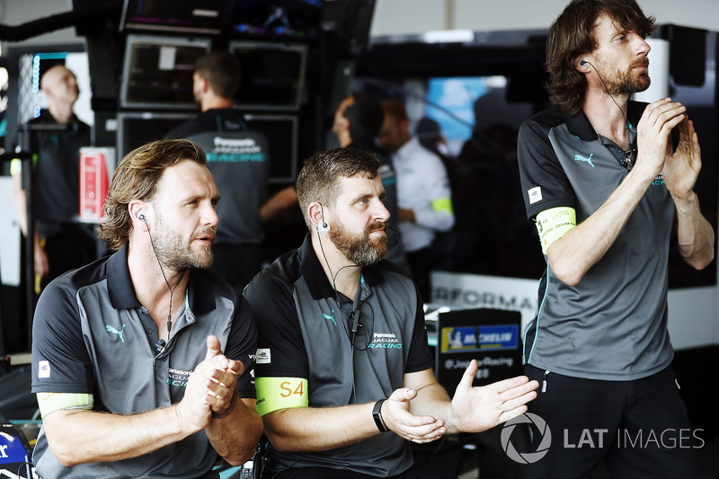 Jaguar Racing team members applaud in the garage