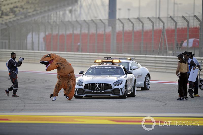 Oficiales de pista con un mensaje para Charlie Whiting, delegado de la FIA en el auto de seguridad que involucra a un dinosaurio