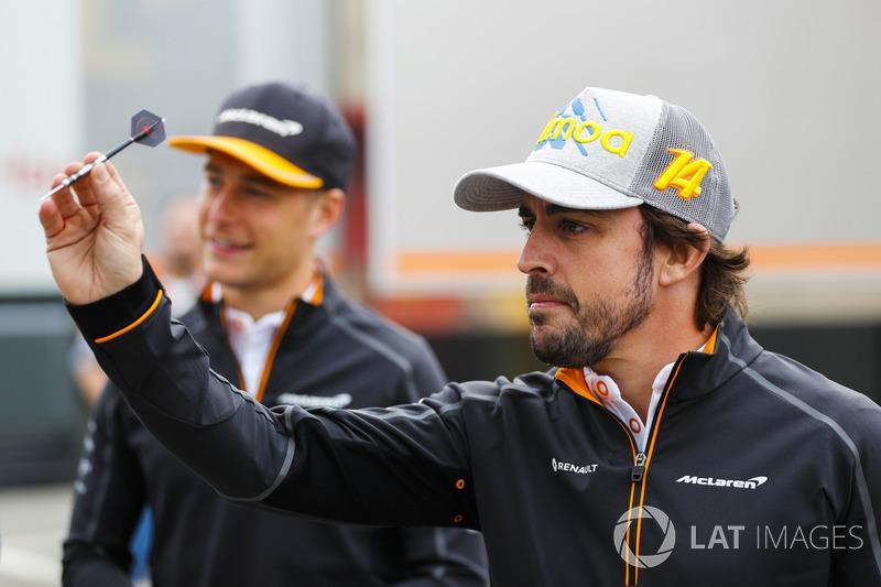 Stoffel Vandoorne, McLaren, and Fernando Alonso, McLaren, play darts