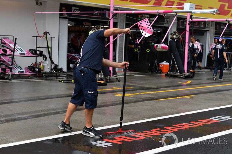 Un meccanico Force India F1 toglie l'acqua dalla piazzola box