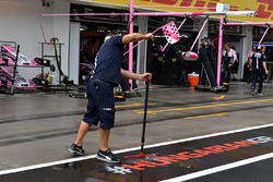 Force India F1 mechanic clears water from the pit box