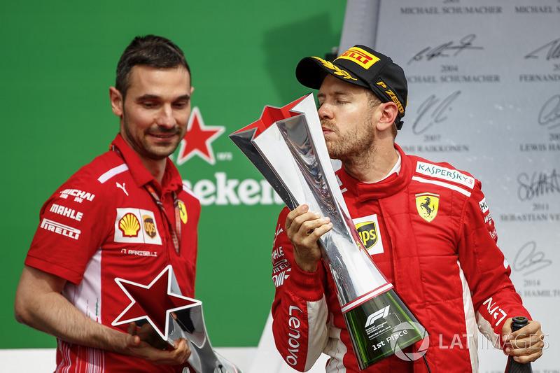 Sebastian Vettel, Ferrari, 1° classificato, bacia il suo trofeo sul podio, accanto a Nicola Bariselli, ingegnere di pista, Ferrari