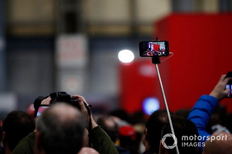 Un fan toma una fotografía de Charles Leclerc siendo entrevistado en el escenario de Autosport
