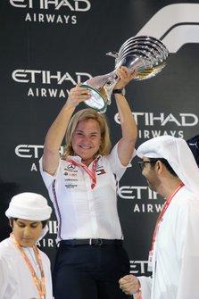 Een teamlid van Mercedes met de contructeurstrofee op het podium