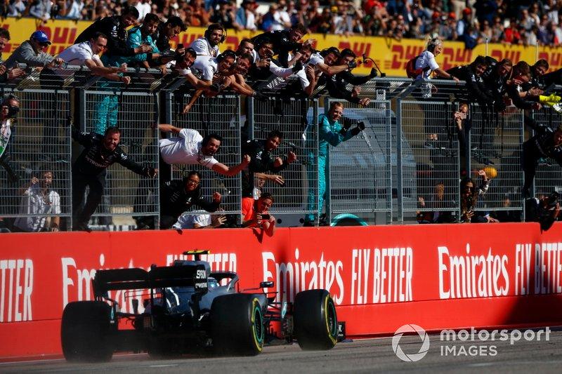 Valtteri Bottas, Mercedes AMG W10, 1° classificato, supera il suo team festante, dopo aver preso la bandiera a scacchi