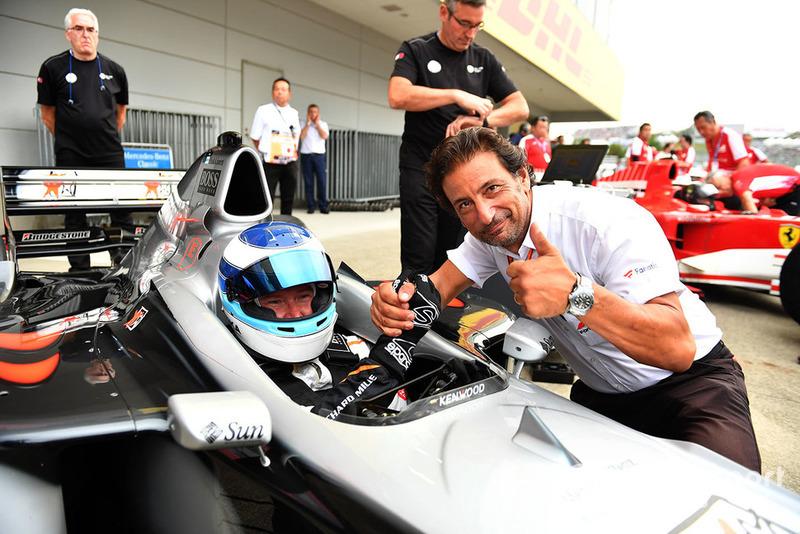 Mika Hakkinen, McLaren MP4-13 y Jean-Michel Tibi, FOM Camarógrafo en Leyendas F1 30 Aniversario vuelta de Demostración