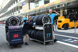 Red Bull Racing mechanic and Mercedes-AMG F1 mechanic with Pirelli tyres