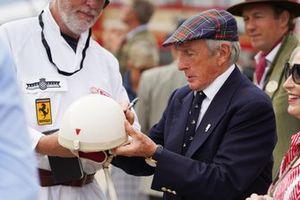 Sir Jackie Stewart firma su autógrafo en un casco