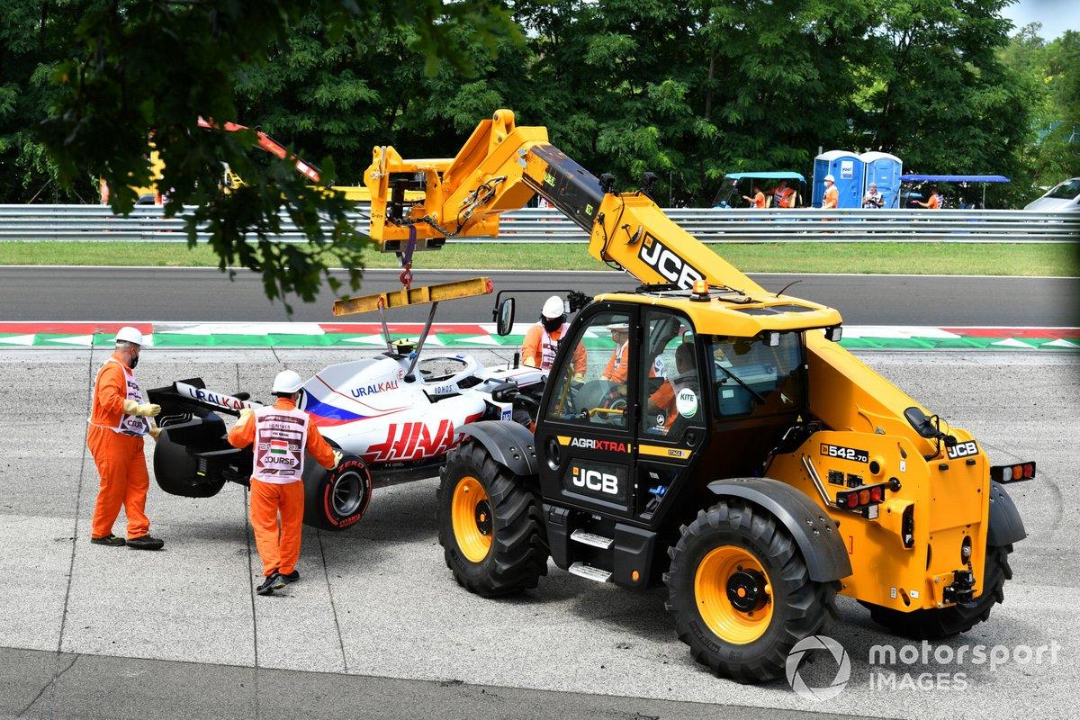 Los oficiales retiran el coche dañado de Mick Schumacher, Haas VF-21, de una barrera de neumáticos tras su accidente en la FP3