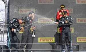 Lewis Hamilton, Mercedes, 1st position, Valtteri Bottas, Mercedes, 3rd position, the Mercedes trophy delegate and Charles Leclerc, Ferrari, 2nd position, spray Champagne on the podium