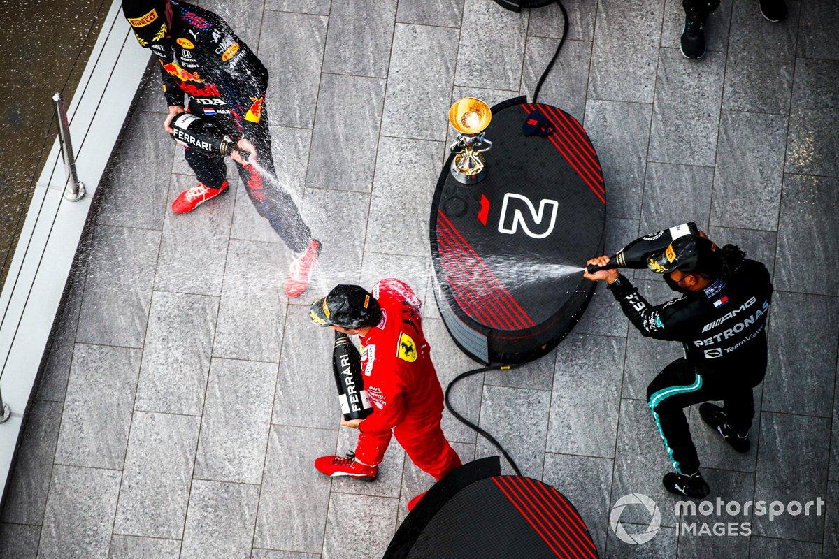 Carlos Sainz Jr., Ferrari, 3a posizione, Max Verstappen, Red Bull Racing, 2a posizione, e Lewis Hamilton, Mercedes, 1a posizione, spruzzano Champagne sul podio