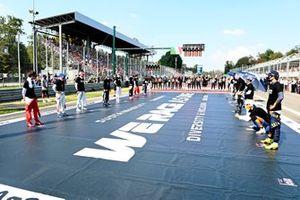 De coureurs staan op de grid voor het volkslied