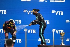 Max Verstappen, Red Bull Racing, 2nd position, and Lewis Hamilton, Mercedes, 1st position, celebrate on the podium with Champagne