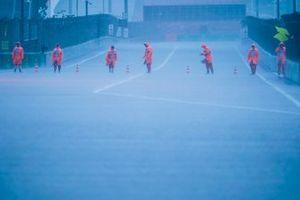 Stewards zetten kegels op de baan terwijl de regen valt