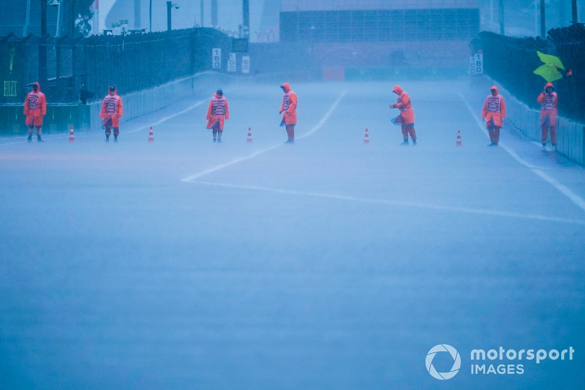 Los comisarios colocan conos en la pista mientras cae la lluvia en Sochi