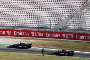 Romain Grosjean, Haas F1 Team VF-19, passes the stopped car of Kevin Magnussen, Haas F1 Team VF-19