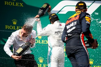 Lewis Hamilton, Mercedes AMG F1, 1st position, and Max Verstappen, Red Bull Racing, 2nd position, celebrate with Champagne on the podium