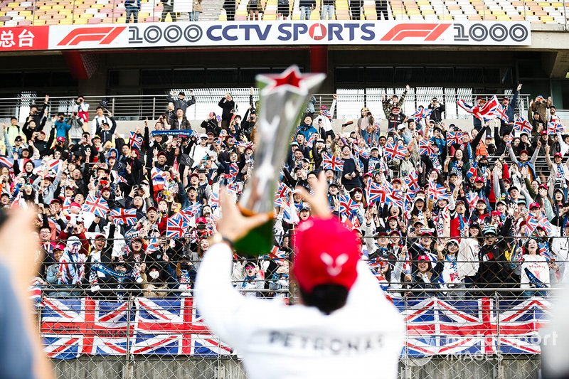 Lewis Hamilton, Mercedes AMG F1, 1st position, displays his trophy to his fans