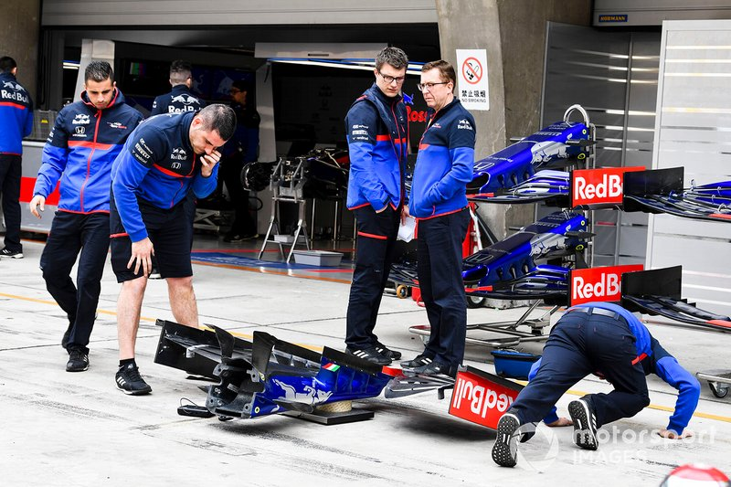 Toro Rosso mechanics inspecting Toro Rosso STR14 front wing