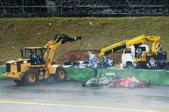 Michael Schumacher, Ferrari F2002 crashes out of the race at Curva do Sol and nearly collects the stricken car of Antonio Pizzonia, that marshals are removing from the track
