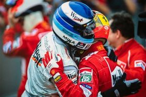 Mika Häkkinen, 2nd position, congratulates Michael Schumacher, 1st position, on victory and on securing the drivers' world championship
