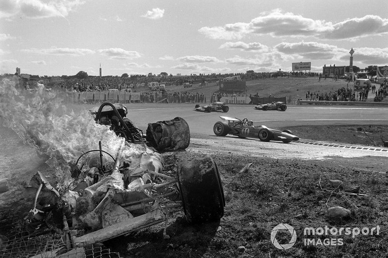 Bruce McLaren, McLaren M14A Ford, Graham Hill, Lotus 49C Ford, y Rolf Stommelen, Brabham BT33 Ford, pasan un un coche en llamas