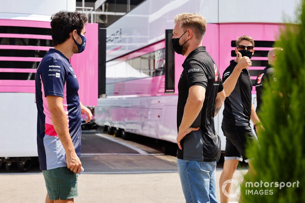 En su regreso al paddock tras una ausencia forzada por un virus, Sergio Pérez, de Racing Point, habla con Kevin Magnussen, de Haas F1, mientras Romain Grosjean, de Haas F1, da el visto bueno