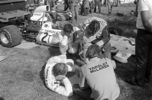 Denny Hulme and Brian Redman go over data with the team in the paddock