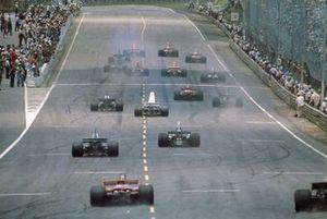 Vista trasera de la salida mientras Niki Lauda lleva a James Hunt y al resto del campo por la colina hacia la curva 1