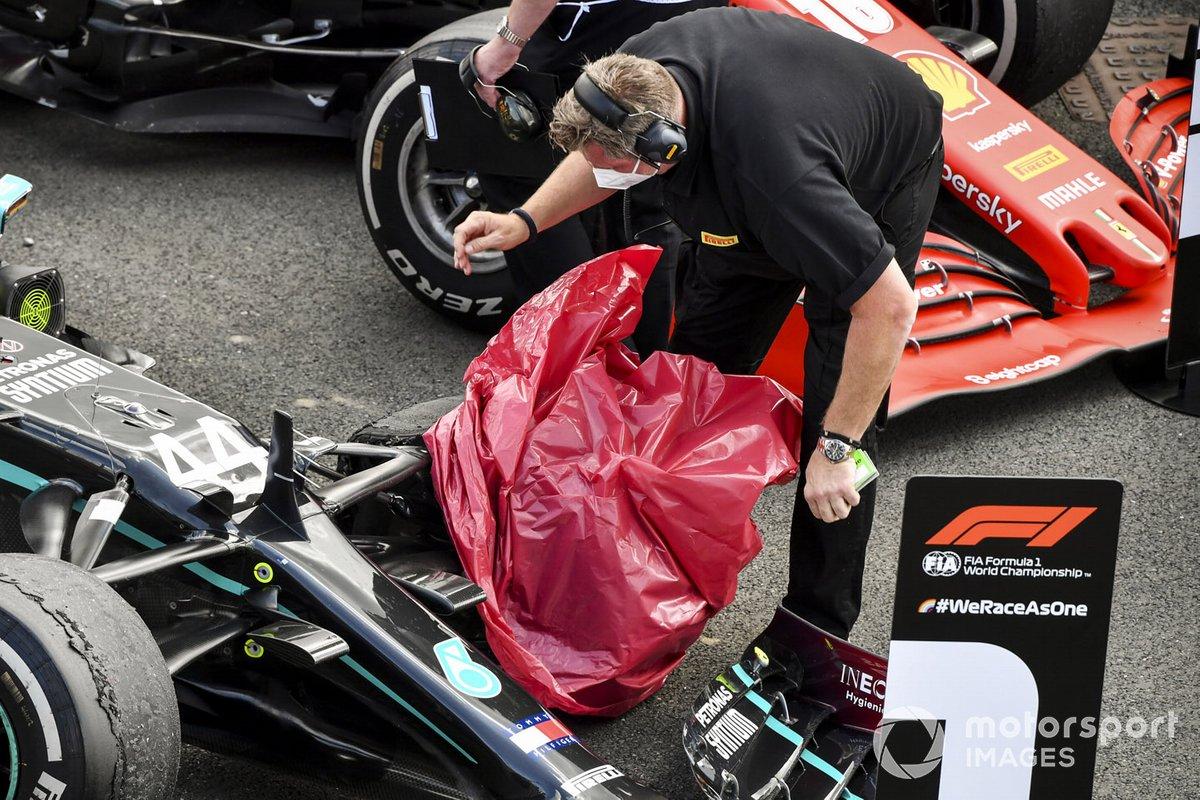 Un técnico de Pirelli cubre el neumático pinchado de Lewis Hamilton, Mercedes F1 W11, en el Parc Ferme