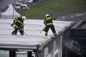 Пожарные удаляют воду с крыши во время дождя