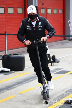 Valtteri Bottas, Mercedes, rides a scooter