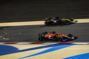 Carlos Sainz Jr., McLaren MCL35, passes Daniel Ricciardo, Renault F1 Team R.S.20, as sparks fly