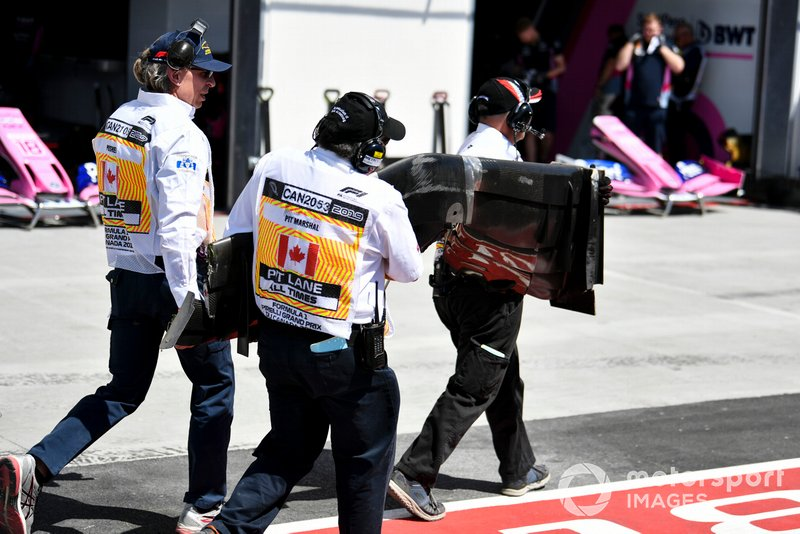Marshals return the front wing of Kevin Magnussen, Haas VF-19, to the pits