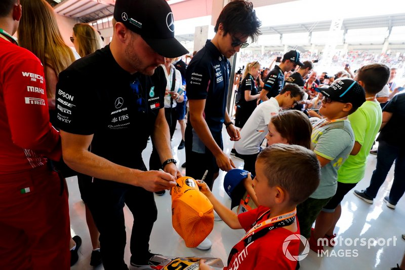 Valtteri Bottas, Mercedes AMG F1, and Lance Stroll, Racing Point, sign autographs for young fans