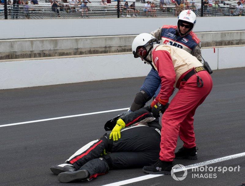 El personal médico ayuda al miembro del equipo herido cuando Jordan King, Rahal Letterman Lanigan Racing Honda, se deslizó dentro de su box y pegó un neumático que lo golpeó