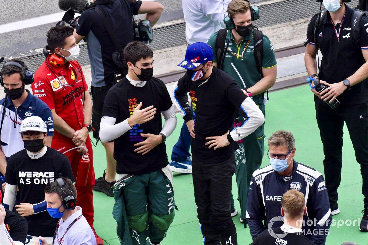 Lance Stroll, Aston Martin, habla con Esteban Ocon, Alpine F1, en la parrilla