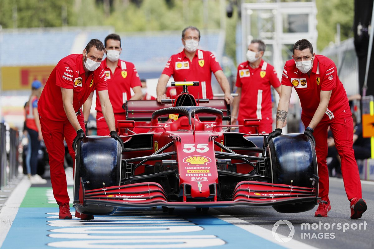Los mecánicos de Ferrari empujan el coche de Carlos Sainz Jr., el Ferrari SF21, por el pitlane
