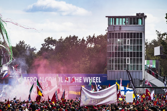 Red smoke and streamers hang in the air as Kimi Raikkonen, Ferrari, second position, Lewis Hamilton, Mercedes AMG F1, first position, and Valtteri Bottas, Mercedes AMG F1, third position, celebrate on the podium