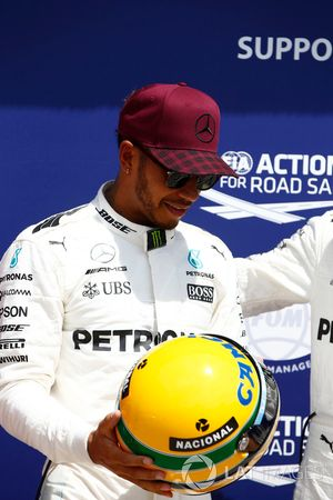 Lewis Hamilton, Mercedes AMG F1, shows off his Ayrton Senna helmet, a gift after equalling the Brazi