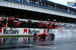 Le vainqueur Michael Schumacher, Ferrari F310, sous le drapeau à damier