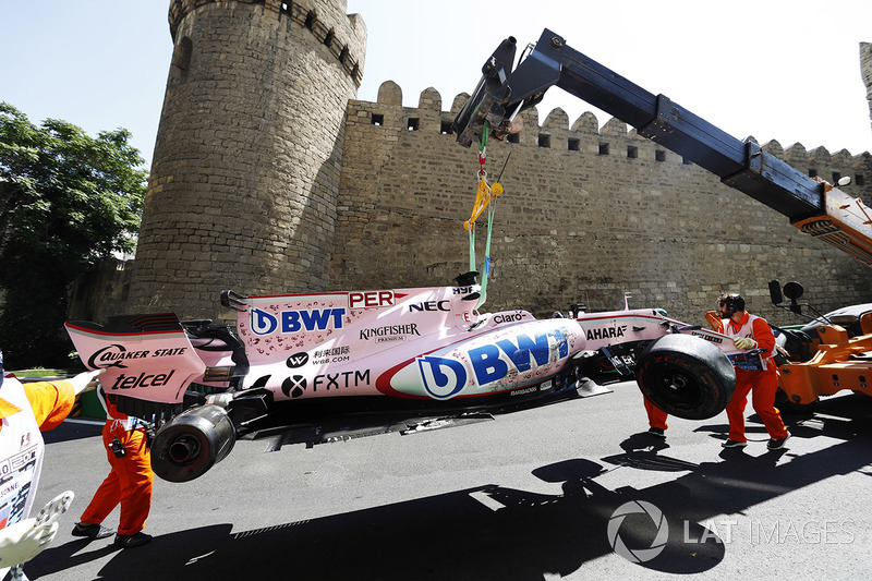 Marshals clear away the crashed Sergio Perez Sahara Force India F1 VJM10, a tow truck