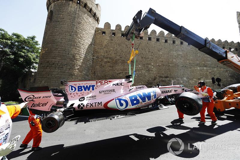 Oficiales de pista remueven el coche chocado de Sergio Pérez Sahara Force India F1 VJM10, en una grú